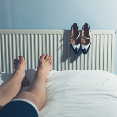 Woman resting on bed after walking in high heels